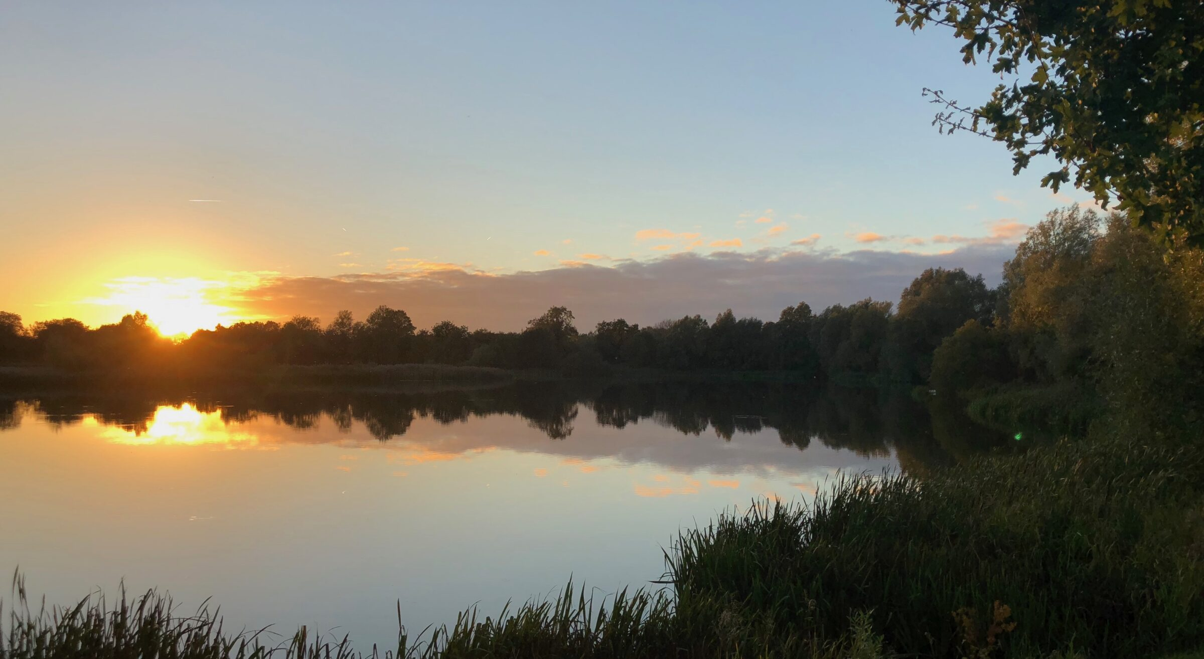 Sunrise over a lake in The Cotswolds